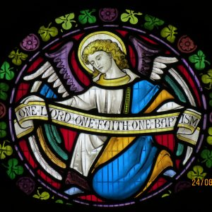 "Stained glass - Angel holding a banner with ""One Lord, One Faith, One Baptism"""